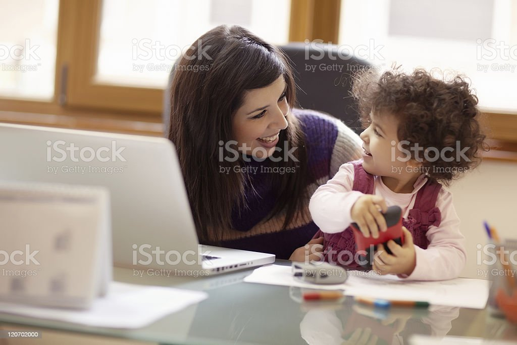 Multitasking mother with her daughter stock photo