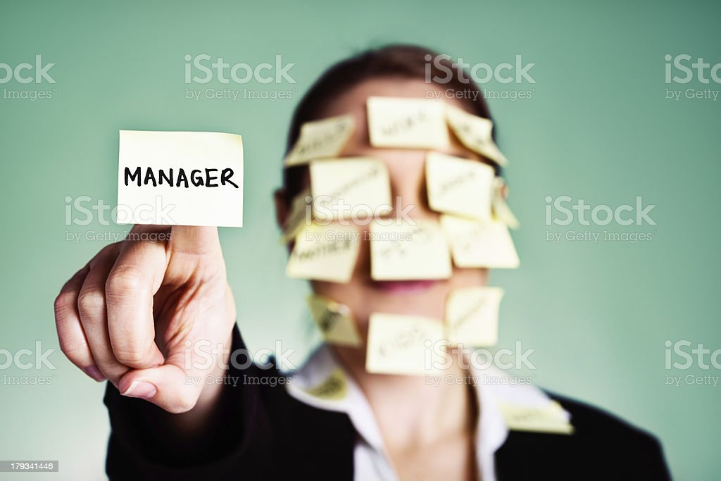 Multitasking woman obscured by task reminders holds sign: MANAGER stock photo