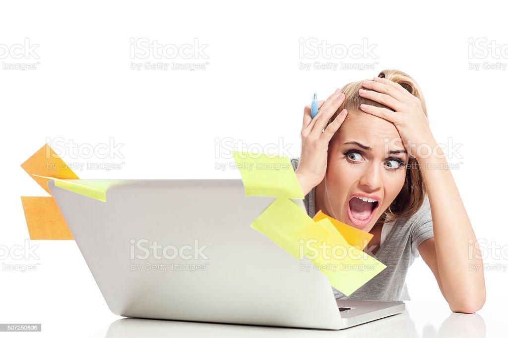Multi-tasking. Young woman using laptop, having panic attack stock photo