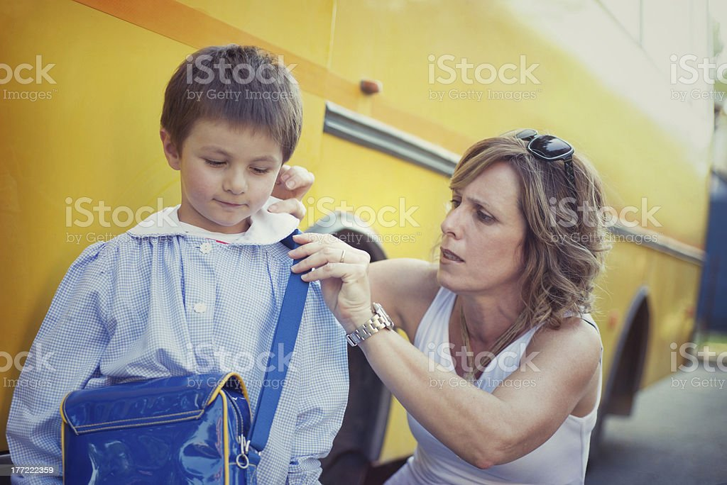 Mum adjusting her child's clothes before school royalty-free stock photo