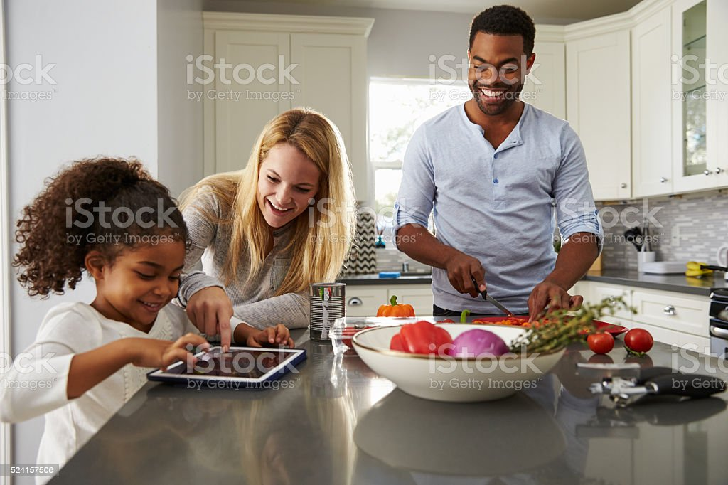 Mum and daughter use tablet computer, and dad prepares food stock photo