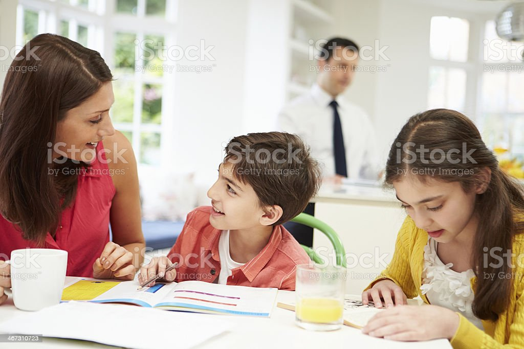 Mum Helps Children With Homework As Dad Works In Background stock photo