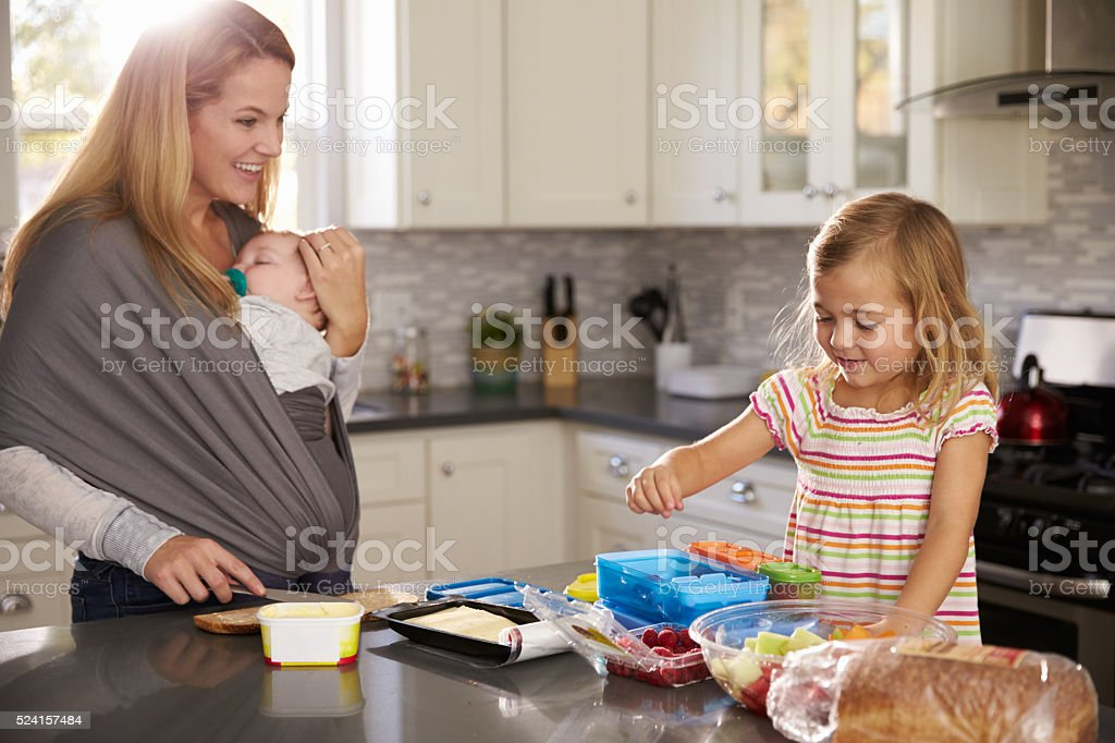 Mum holding baby watches older daughter preparing food stock photo