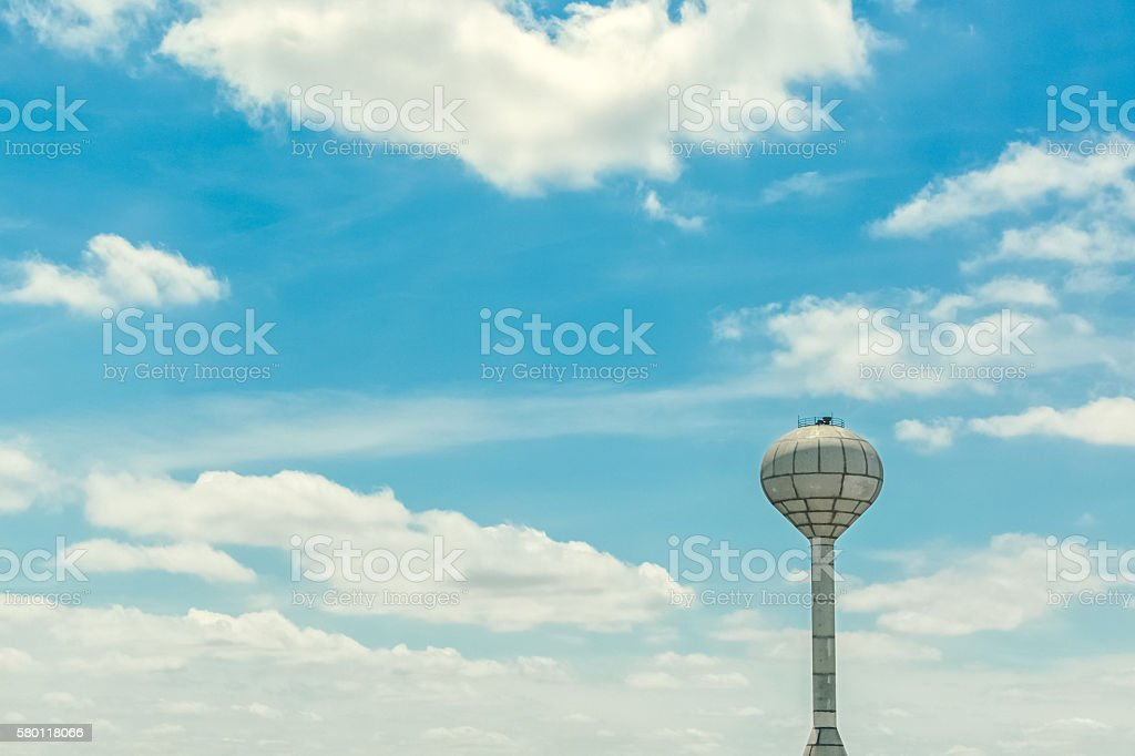 Municipal Water Tower Against Blue Sky With White Clouds stock photo