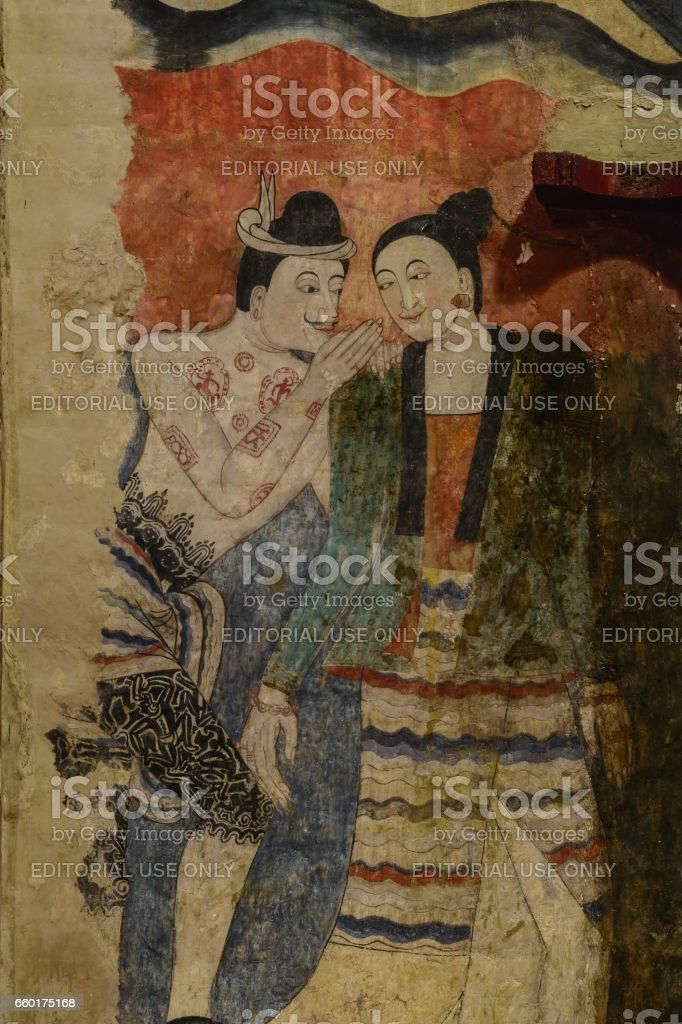 Mural painting of a man whispering to the ear of a woman. stock photo
