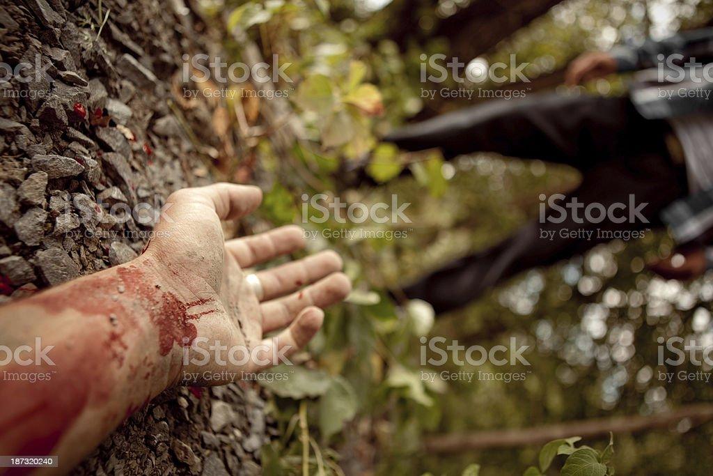 Murdered man's hand lying on the ground stock photo