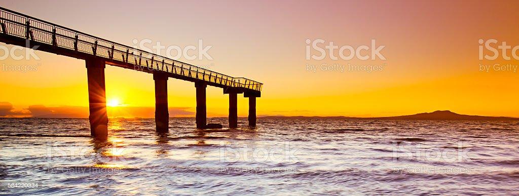 Murrays Bay Sunrise through Jetty stock photo