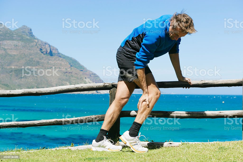 Muscle cramp in calf stock photo