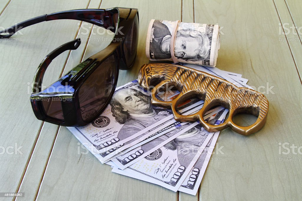 Muscle for hire: brass knuckles and cash stock photo