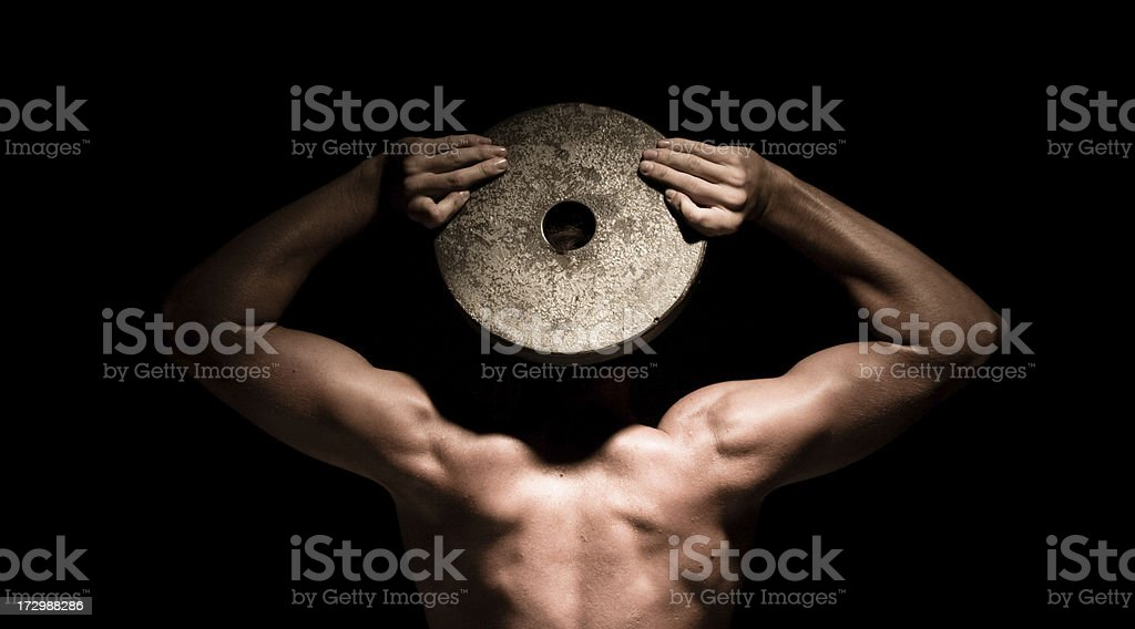 Muscle head - muscular man holding a weight over face royalty-free stock photo