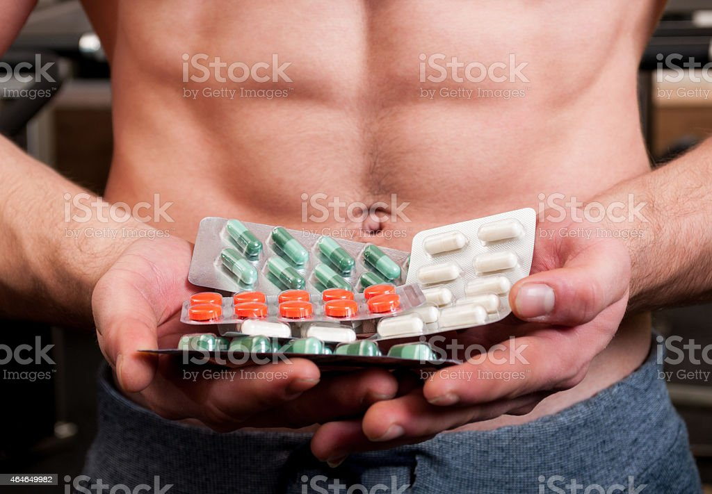 Muscle man holding blisters of pills stock photo