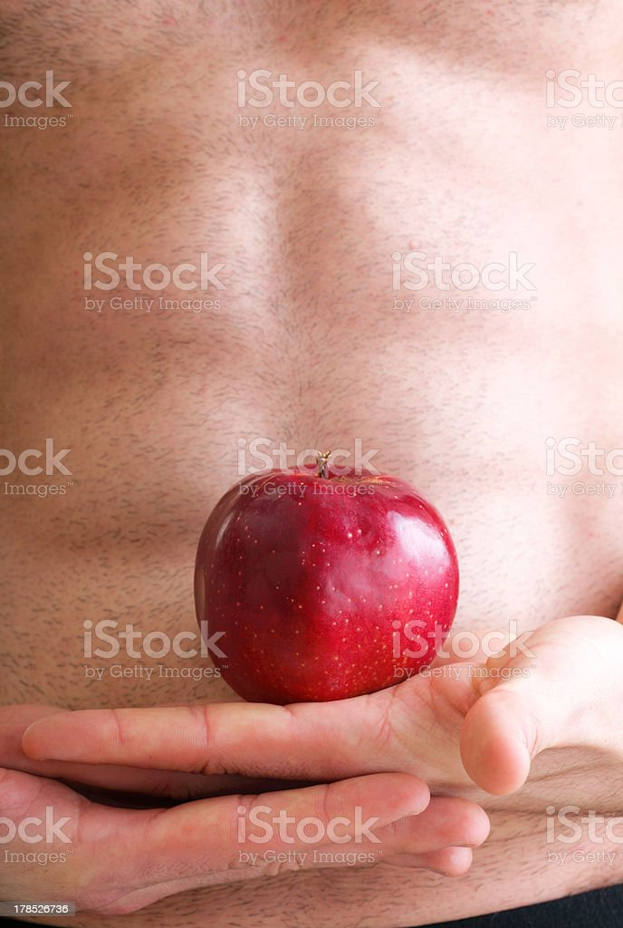 Muscle naked young man torso red apple in hands royalty-free stock photo