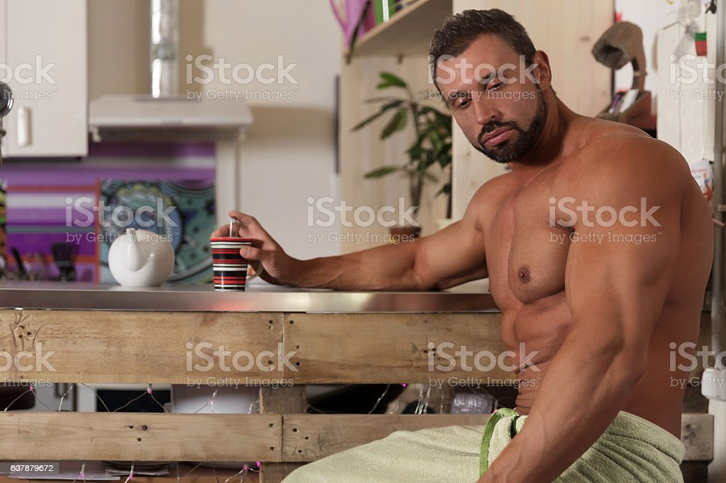 Muscle shirtless bachelor man have a breakfast in kitchen stock photo