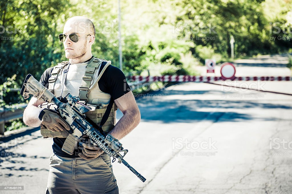 Muscled Modern Mercenary Contractor Soldier Guarding a Roadblock royalty-free stock photo