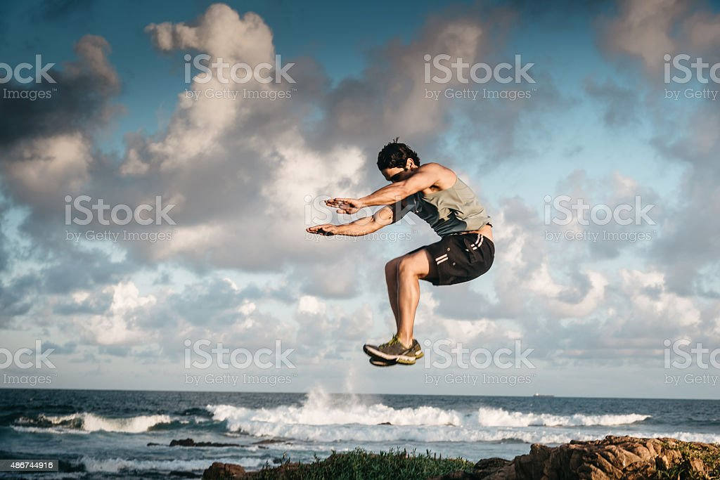 muscled sportsman jumping high at a beach in evening light stock photo