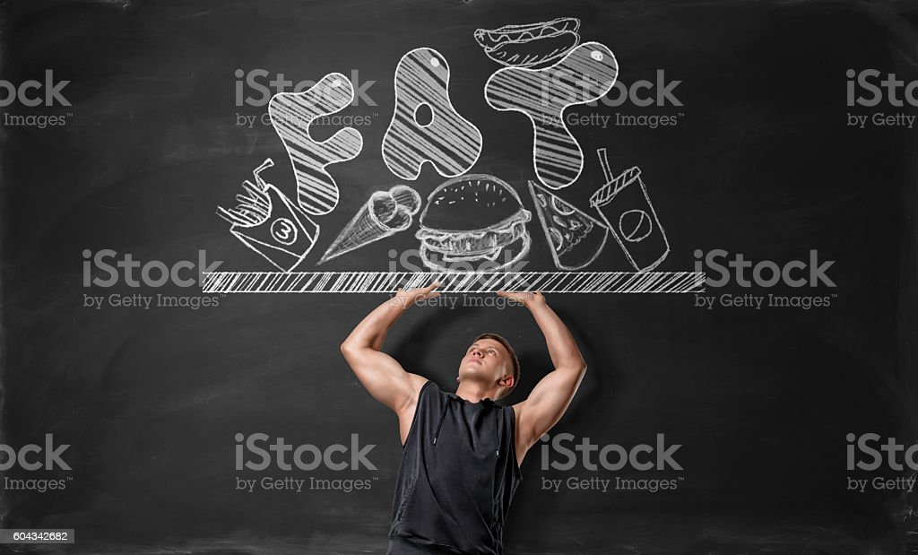 Muscled young man pushing off surface with junk food and stock photo