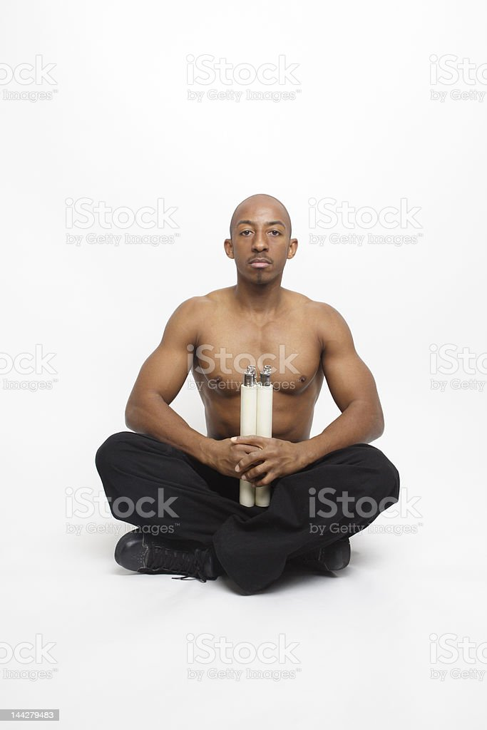 Muscular African American Man Sitting Cross Legged Holding Nunchucks Isolated royalty-free stock photo
