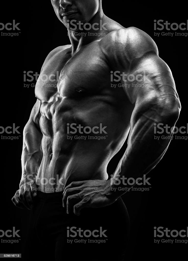 Muscular and fit young bodybuilder fitness male model posing. stock photo