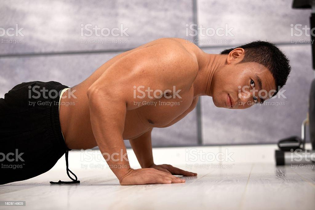 Muscular asian man exercising in gym royalty-free stock photo