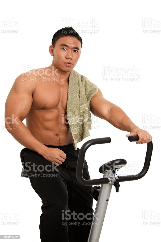 Muscular asian man on exercise bike royalty-free stock photo
