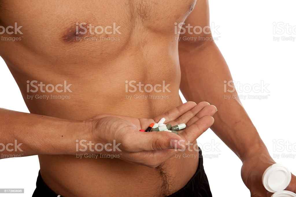 Muscular Asian man show  six pack abs  with some pills stock photo