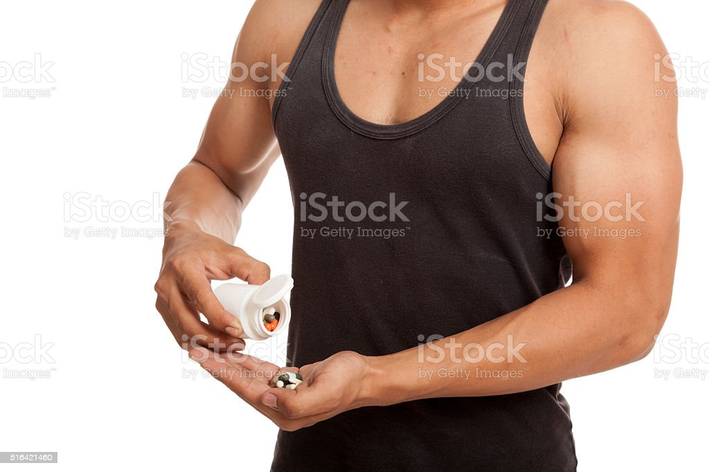 Muscular Asian man with drug pills stock photo