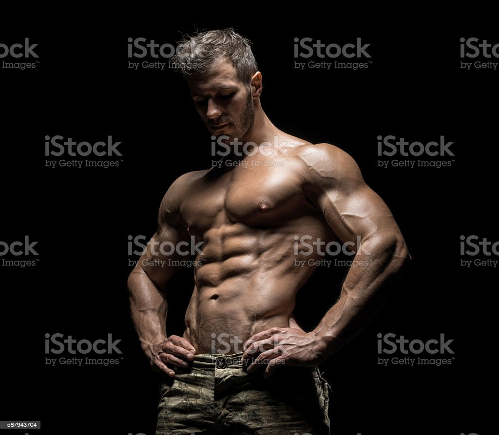 Muscular athlete bodybuilder man on a dark background stock photo