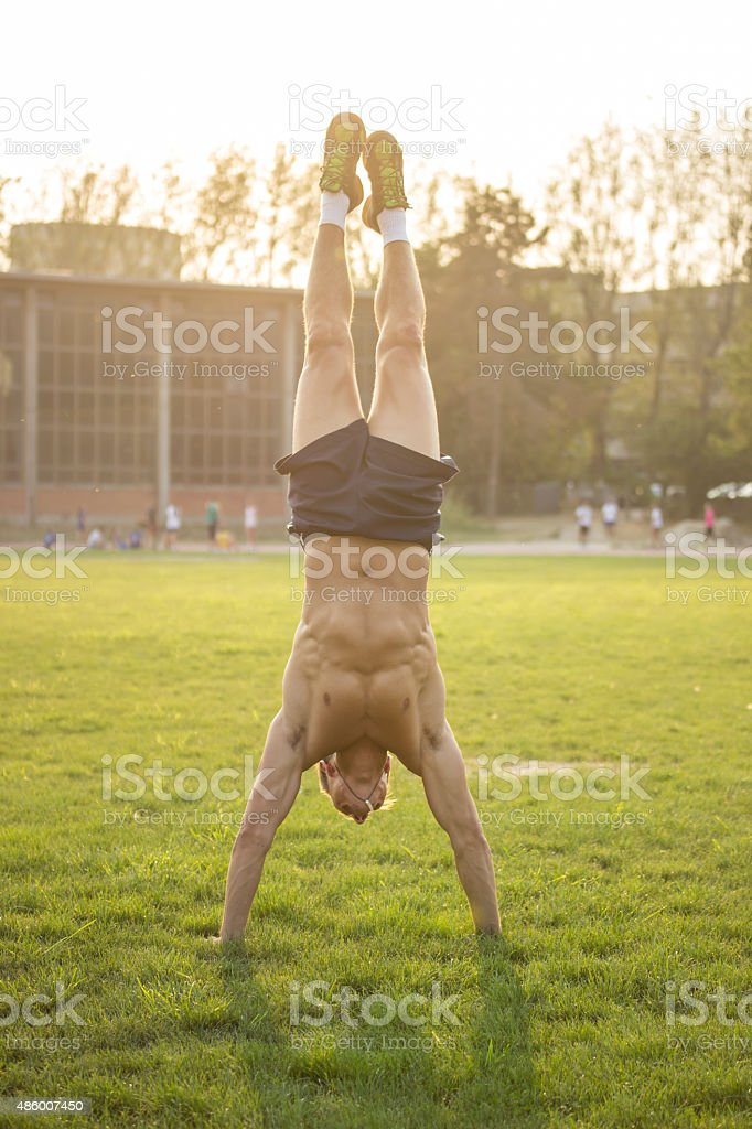 Muscular athlete doing Handstand in grass. stock photo