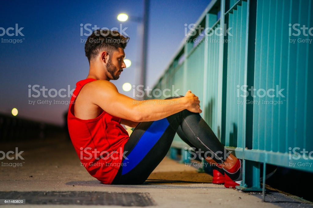 Muscular athlete exercising outdoors, near the road in urban district in summer stock photo