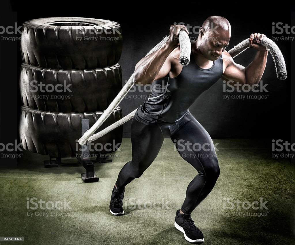 Muscular athlete pulling sled of tires. stock photo