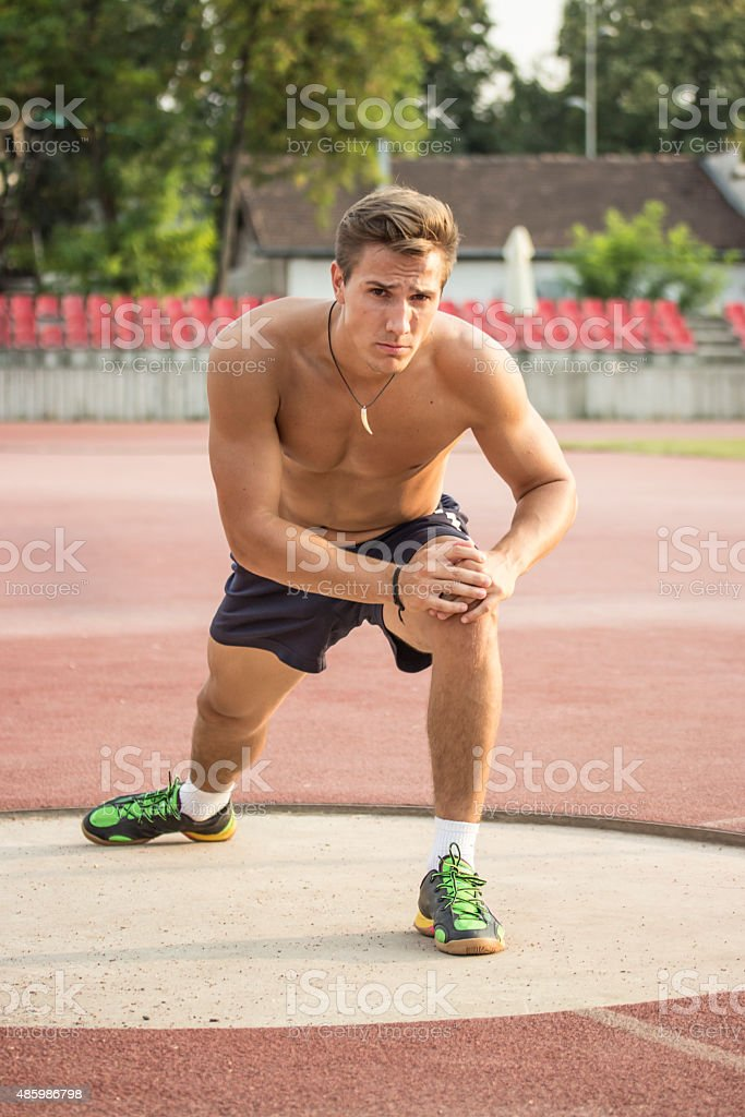 Muscular athlete stretching his legs, looking to camera. stock photo