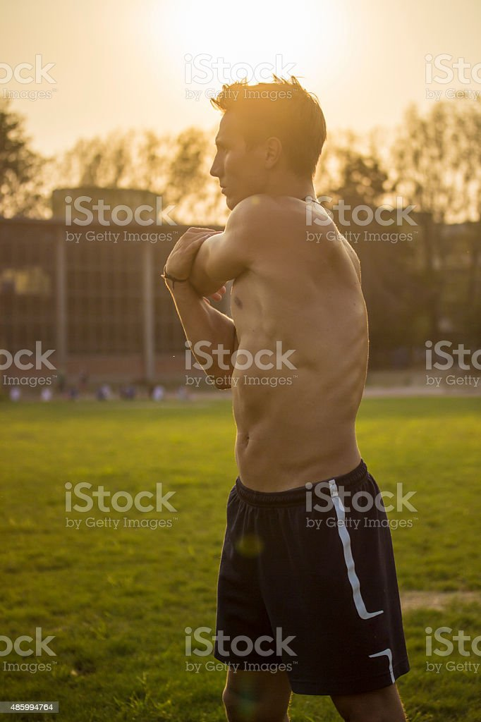 Muscular athlete stretching upper body. Intentionall lens flare. stock photo