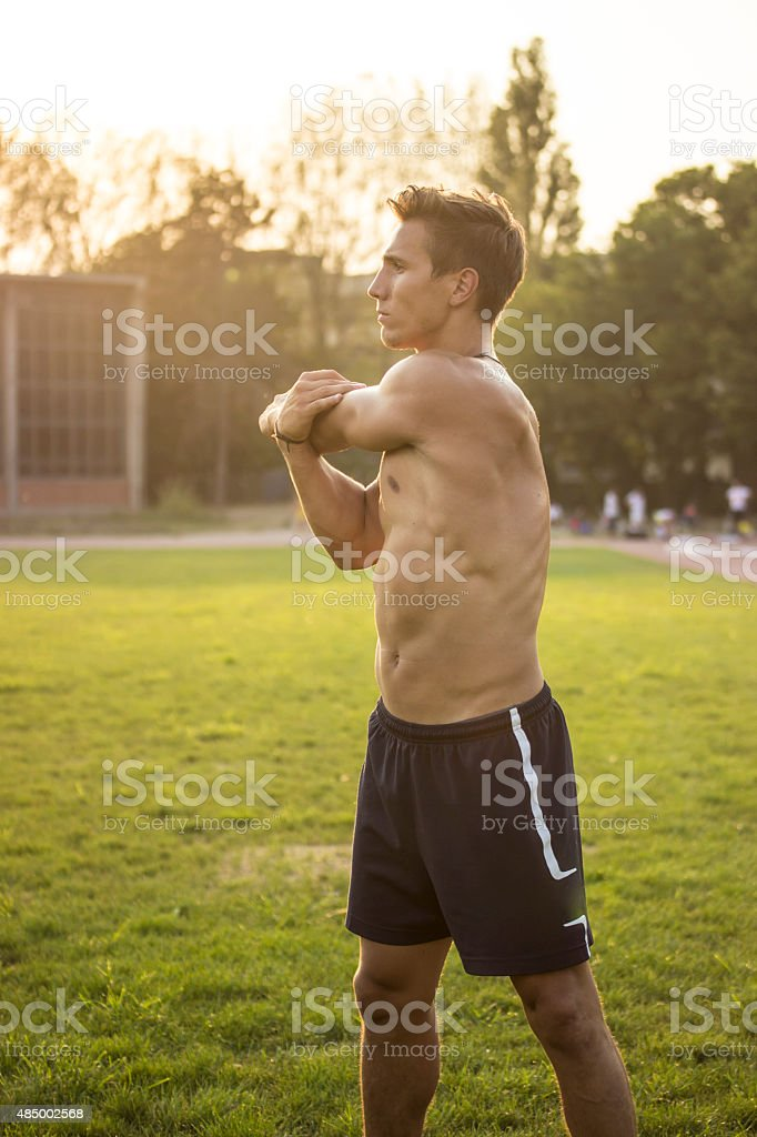 Muscular athlete stretching upper body. stock photo
