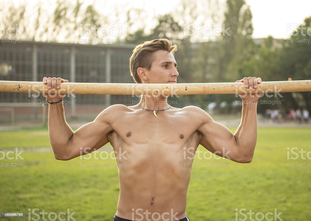 Muscular athlete trainting pull up, upper body shot. stock photo
