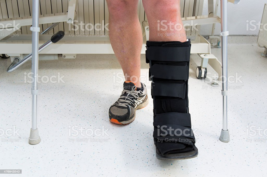 Muscular athlete with Walking boot for achilles tendon treatment stock photo