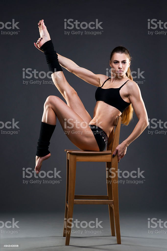Muscular attractive fitness woman on gray background in studio stock photo