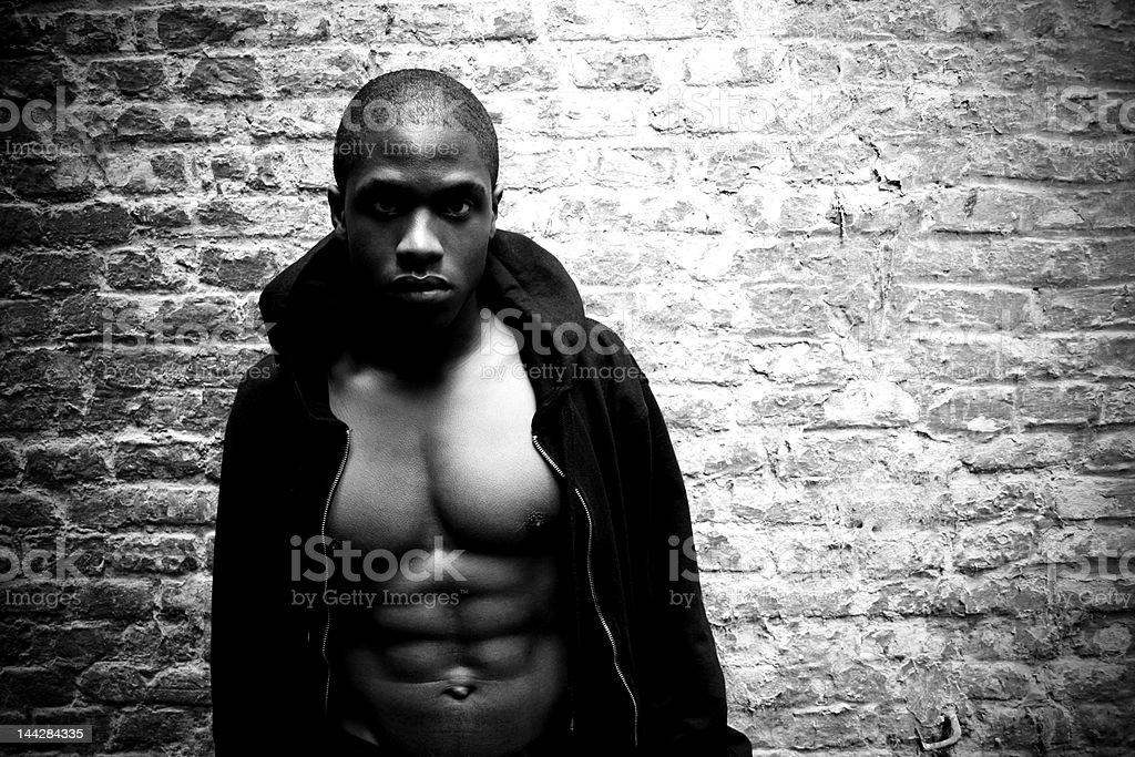 Muscular Black Man Against Brick Wall | b/w version royalty-free stock photo