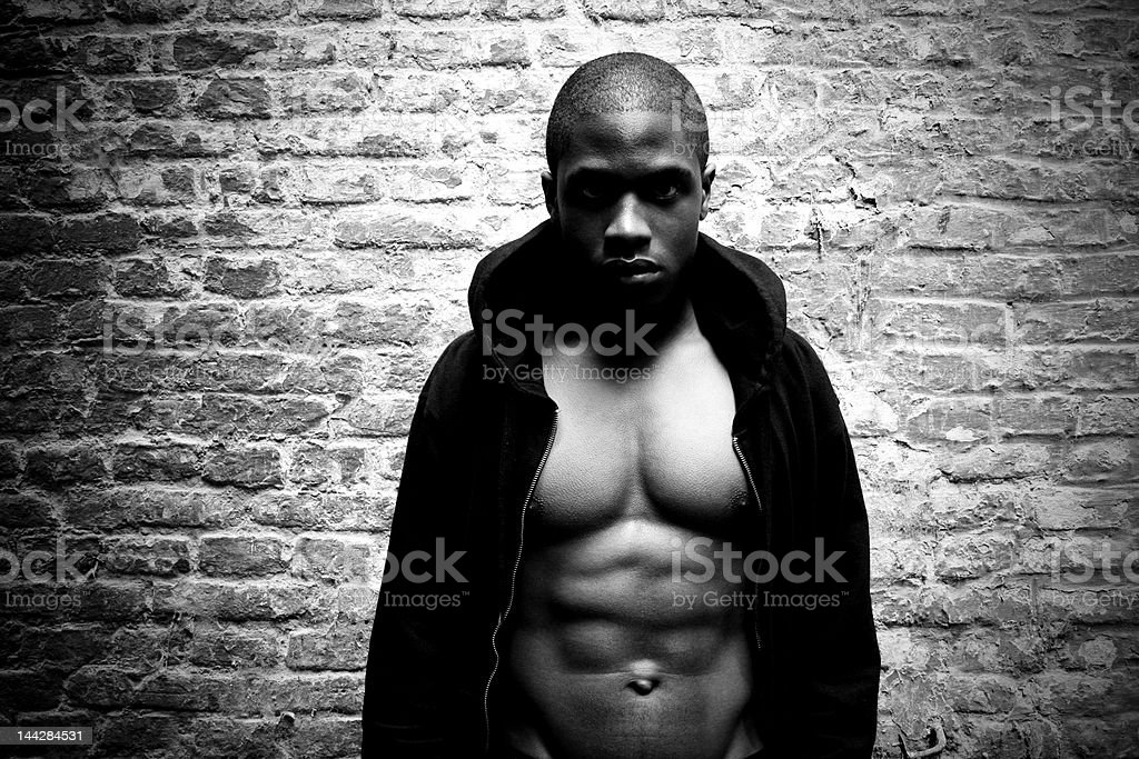 Muscular Black Man Against Brick Wall | b/w version stock photo