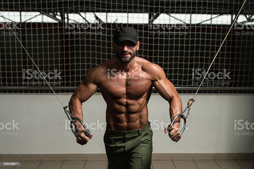 Muscular Bodybuilder Performing Cable Crossover stock photo