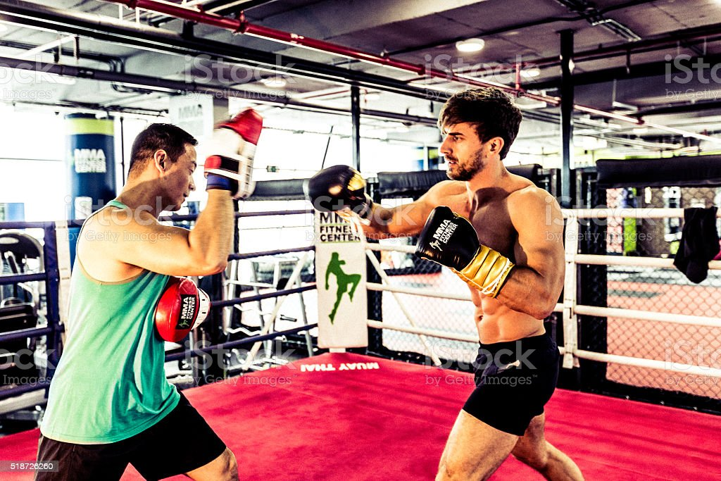 Muscular Boxer Having a Sparring Session with his Trainer stock photo