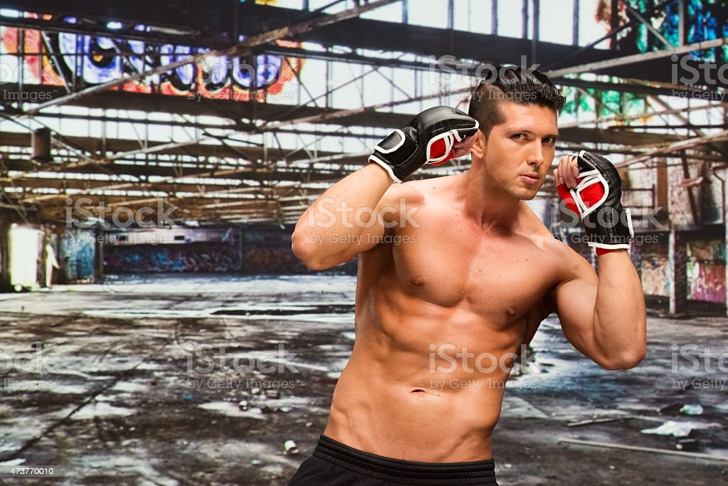 Muscular boxer in warehouse stock photo