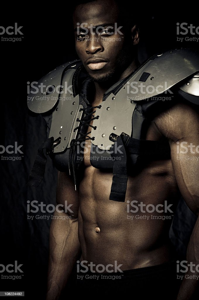 Muscular build: American football player with shoulder pads royalty-free stock photo