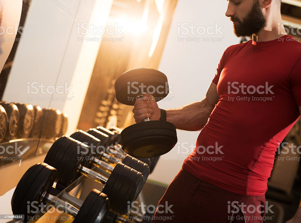 Muscular build man taking dumbbells in a gym. stock photo