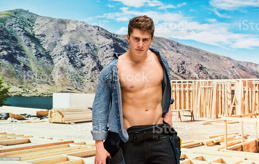 Muscular building contractor in construction site stock photo