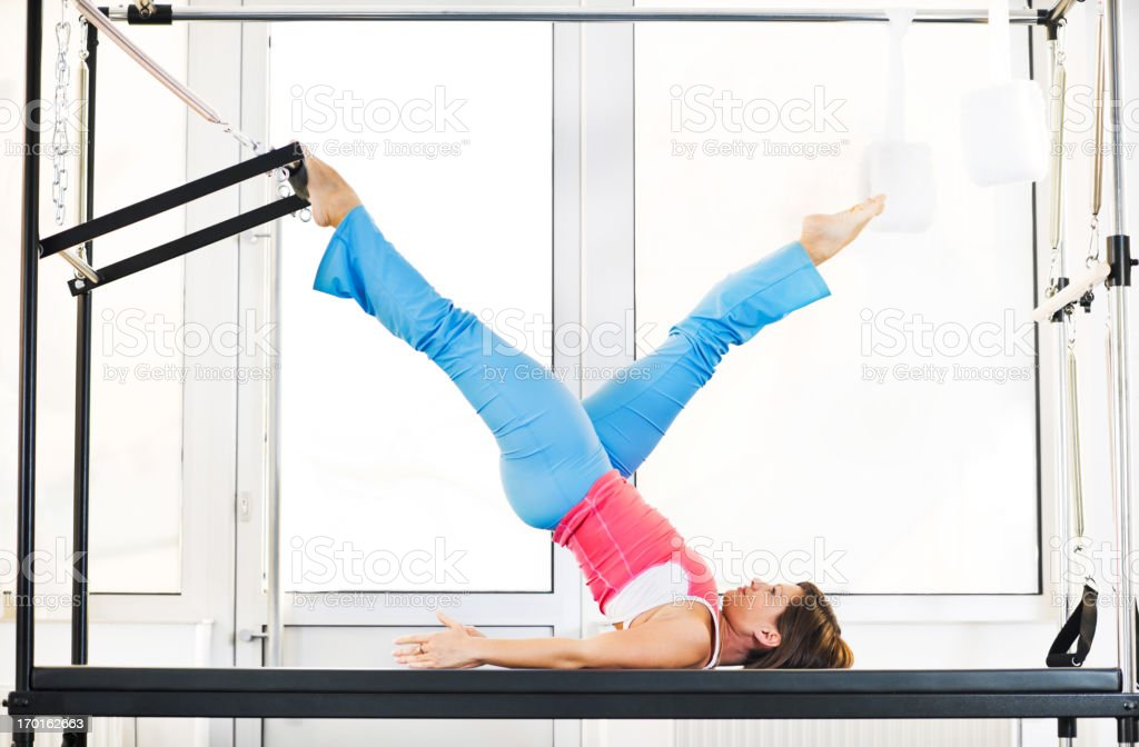 Muscular built woman using exercising equipment at Pilates class royalty-free stock photo