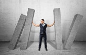 Muscular businessman full-height holding concrete four columns falling on
