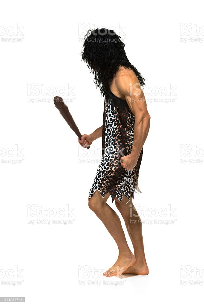 Muscular caveman holding club and walking stock photo