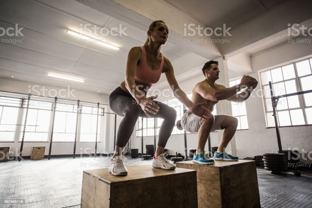Muscular couple doing jumping squats stock photo