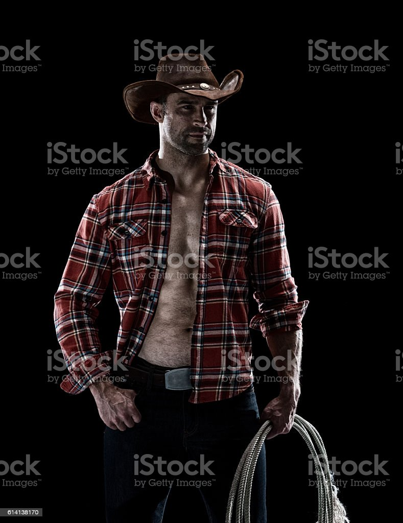 Muscular cowboy holding lasso stock photo