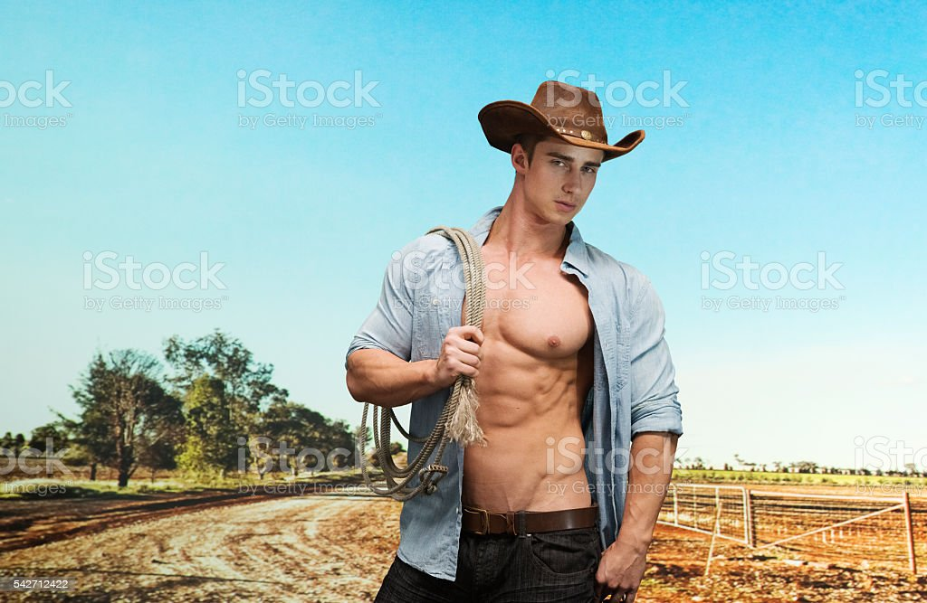 Muscular cowboy standing in field stock photo